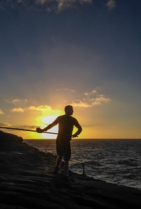 Casting a fishing pole into Hawaii's sunrise