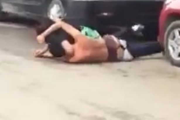 Couple fighting in street as they tear off each other's clothes