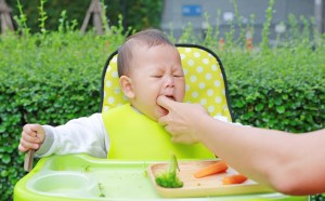 child in high chair choking while mom is trying to grab it out of mouth