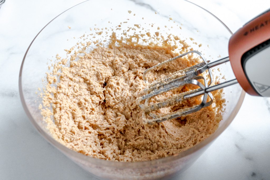 Batter in a bowl with an electric whisk.