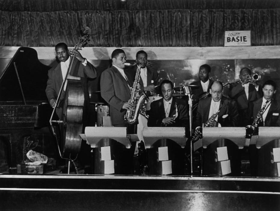 1953 – Count Basie's Orchestra on stage at the Savoy Ballroom. Musicians: Eddie Jones, Frank Wess, Gus Johnson, Ernie Wilkins, Freddie Green, Marshall Royal, Reunald Jones, Frank Foster. Source: Frank Driggs Collection, Magnum Photos (reference PAR60147).