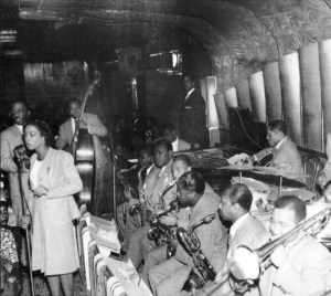 c.1940s Erskine Hawkins & His Orchestra. Musicians are: singer Dolores Brown, Hawkins behind her, bassist Lee Stanfield, Captain Ed Sims, Haywood Henry, Julian Dash, Jimmy Mitchelle, William Johnson, Paul Bascomb, Avery Parrish, William McLemore. Source: unknown.