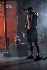 Tired athlete topless wipes the sweat from his forehead