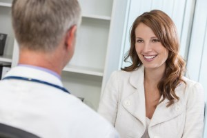 Happy Woman Patient Meeting With Male Doctor in Office