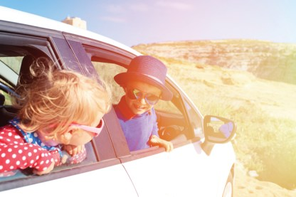 cute little boy and girl travel by car in mountains