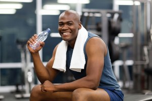 young african man drinking water after exercise