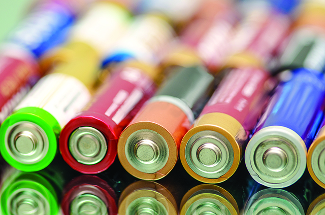 Closeup of pile of used alkaline batteries. Closeup colorful rows of AA storage batteries
