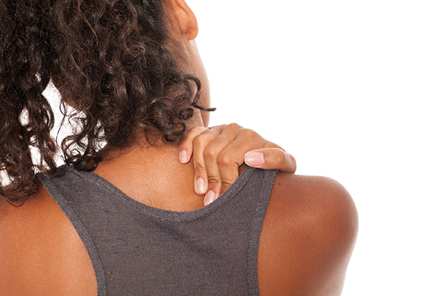 back view of dark skinned girl massaging her neck on white background