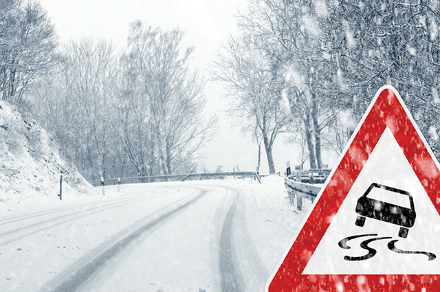 Snowy curvy road with traffic sign