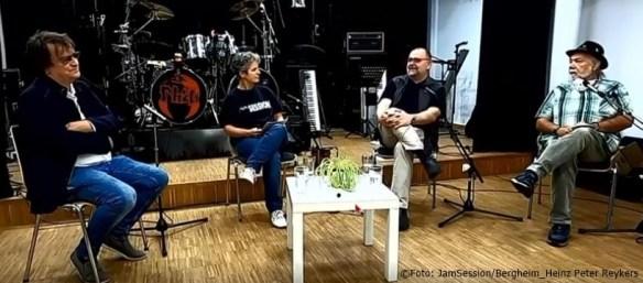 Eine Bühne mit Schlagzeug, im Vordergrund sitzen (von links) ein Mann, eine Frau, ein Mann, ein Mann.