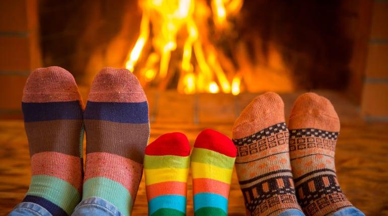 Füße einer Familie mit Kind vor einem Kaminfeuer