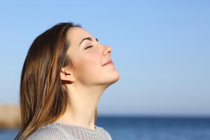 woman breathing deeply beside ocean