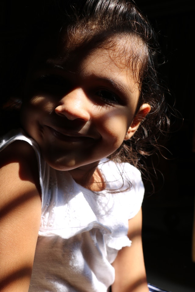 Smiling little girl in sunlight looking at camera