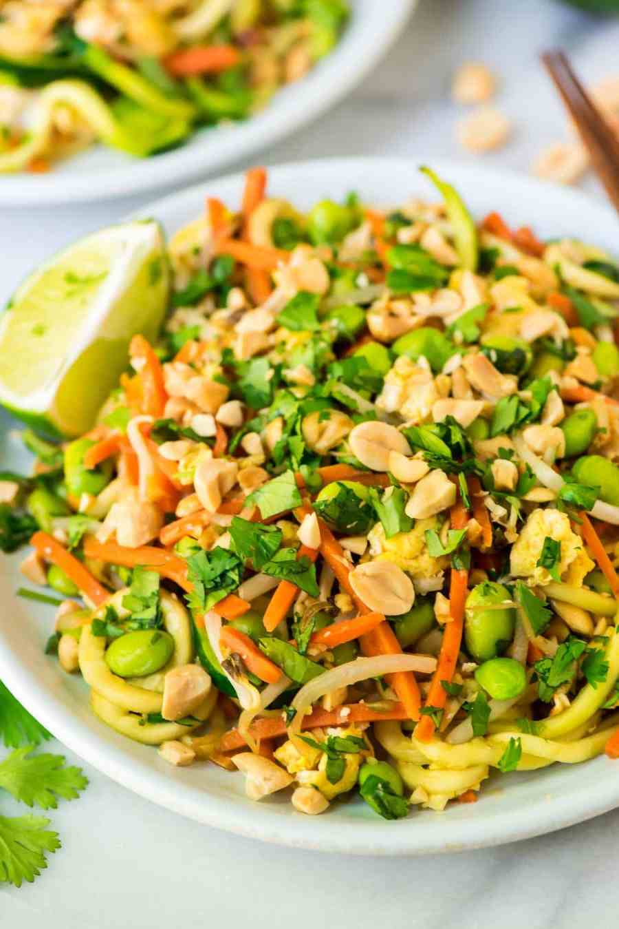 Zoodle Pad Thai in a white bowl with chopsticks and garnished with lime wedges, cilantro and peanuts