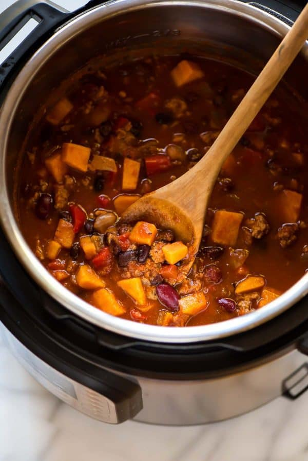 How to make THE BEST Instant Pot Chili. Cooks in just 10 minutes! Easy, healthy, low carb recipe with ground turkey, canned beans, and sweet potatoes.