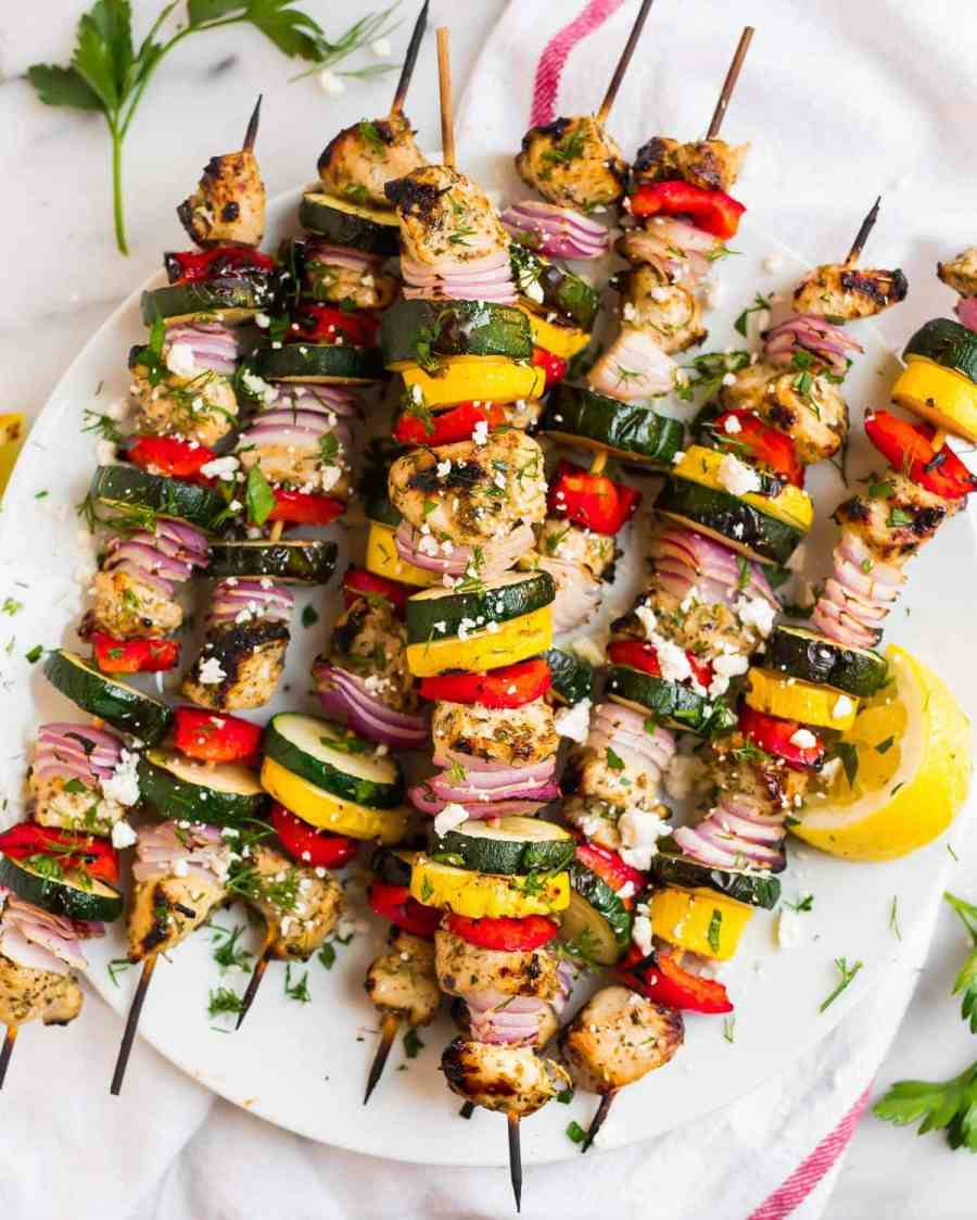Healthy grilled chicken kabobs with vegetables on a white plate