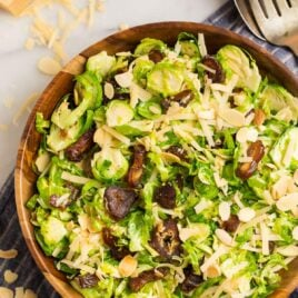 Fresh and healthy brussels sprouts slaw made with shredded brussels sprouts in a honey lemon Dijon dressing, inside of a wood bowl