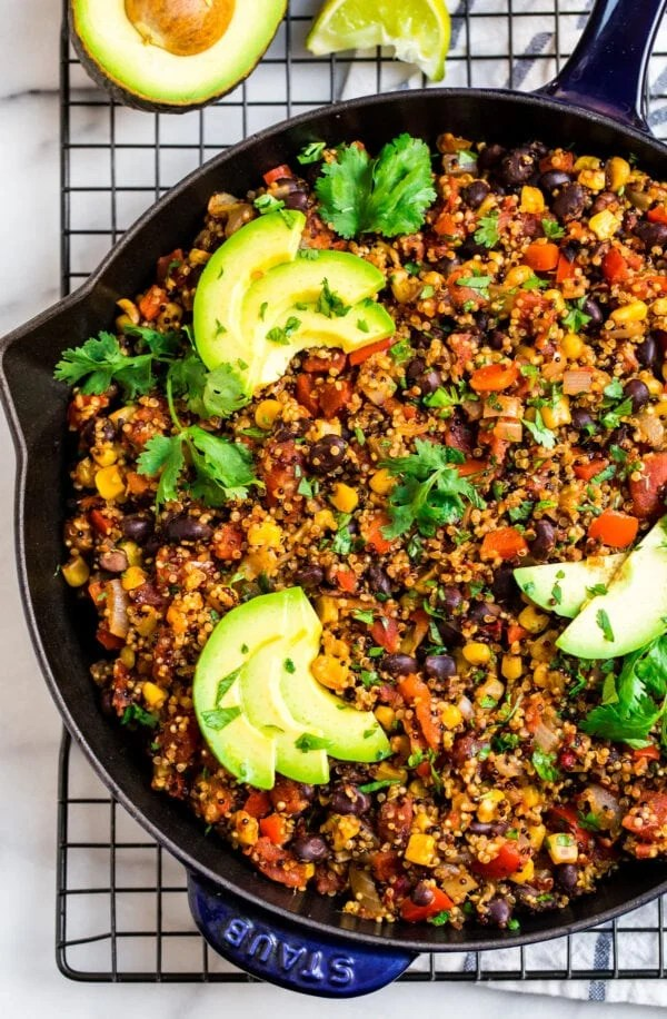 A skillet of quinoa, black beans, corn, and Mexican spices topped with avocado