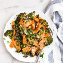 Roasted broccoli and carrots on a plate with Parmesan
