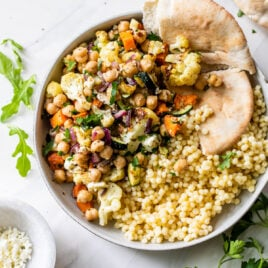 Roasted vegtable salad in a bowl with quinoa and pita