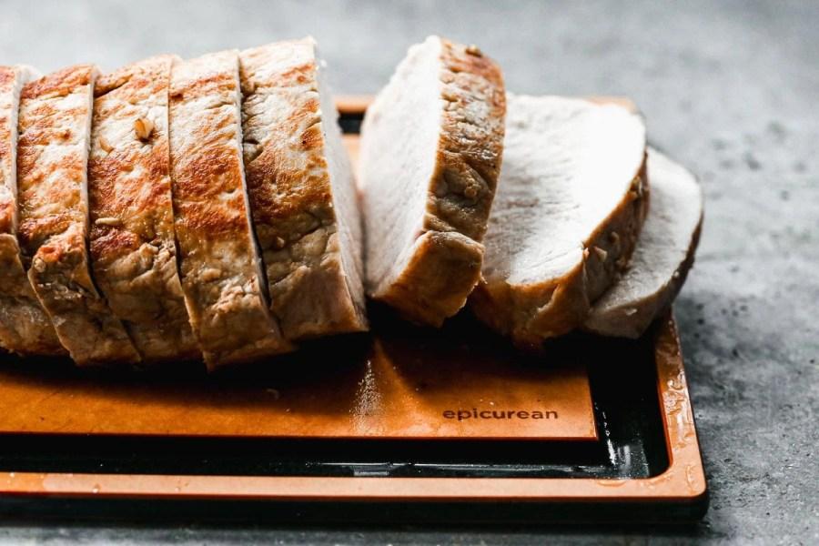 Pork loin being sliced on a cutting board