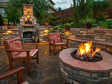 Landscaping backyard with stone fire place and chairs