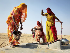 Women taking wter out of a taanka with buckets and pots