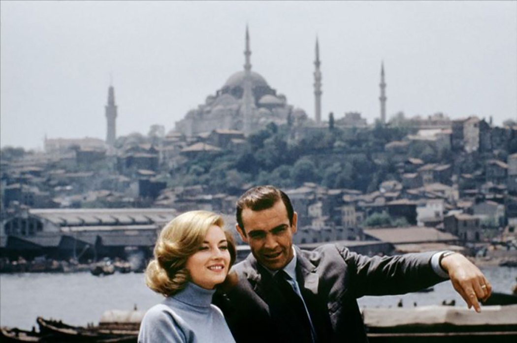 Sean Connery and Daniela Bianchi are standing on the ferry and the Hagia Sophia is in the background