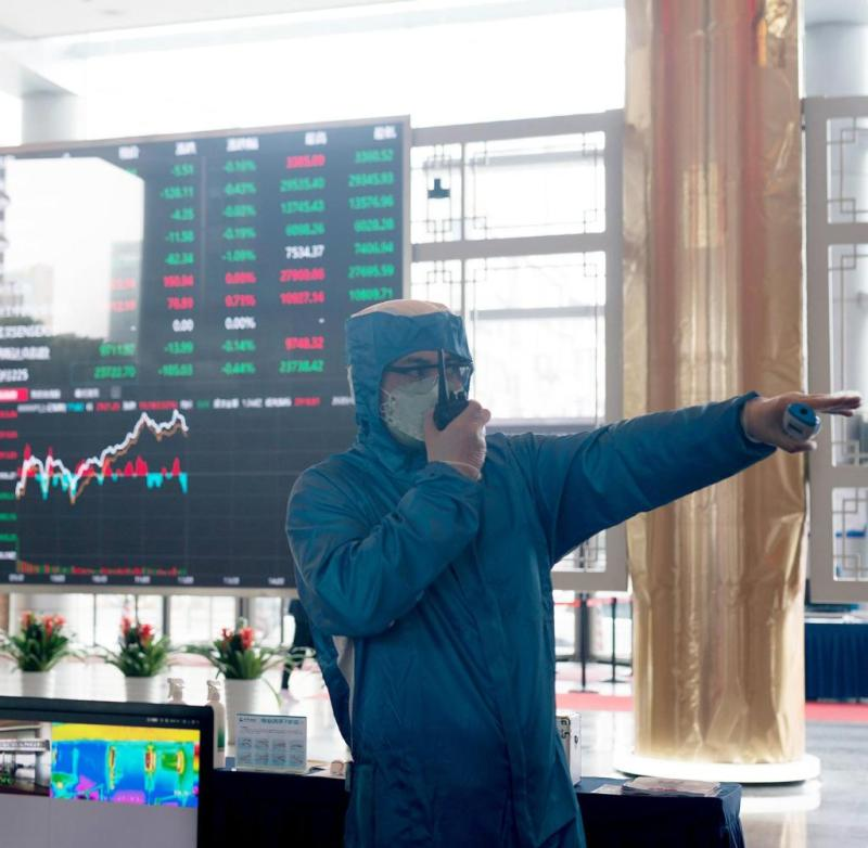 A worker in protective suit in the lobby of the Shanghai Stock Exchange: The corona virus could bring the global economy to the brink of recession