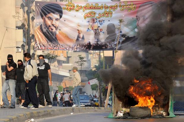 Alltag in Beirut: Regierungsgegner und Hisbollah-Anhänger verbrennen Autoreifen neben einem Transparent mit dem Bild von Hisbollah-Führer Hassan Nasrallah
