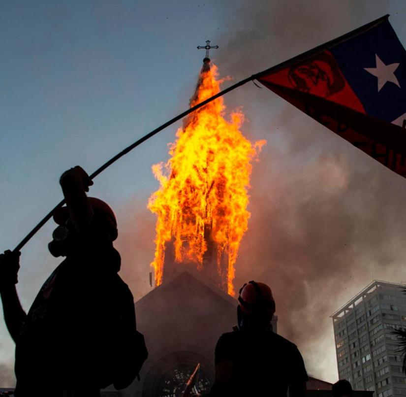 A protester in front of a burning church in Santiago de Chile