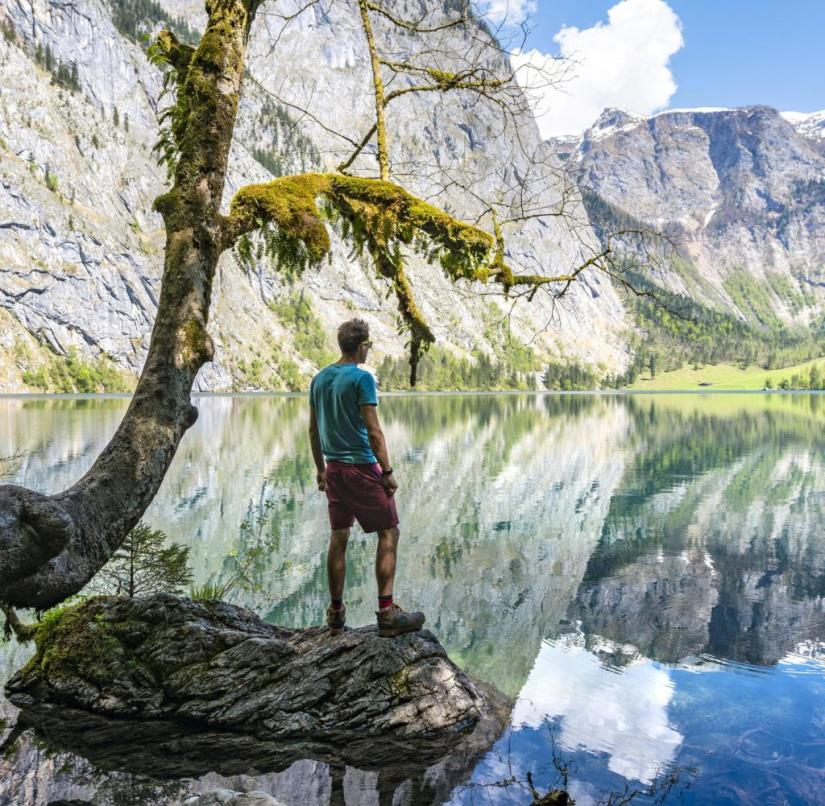 Hiking in Bavaria: A hiker in Berchtesgadener Land takes a break and enjoys the view of the clear Obersee