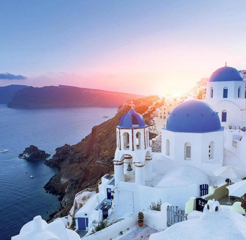 The place Oia is picturesquely located on the steep coast of Santorini in Greece