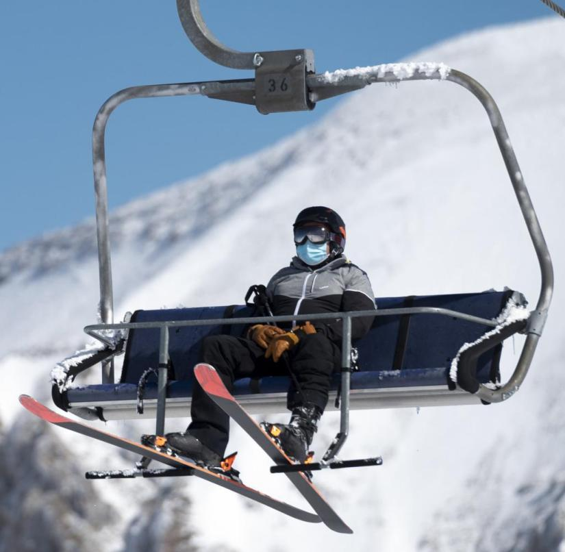 "Switzerland: Switzerland: A skier who wears mouth and nose protection goes on the opening day of the ski area ""Glacier 3000"" in Les Diablerets with a chair lift"