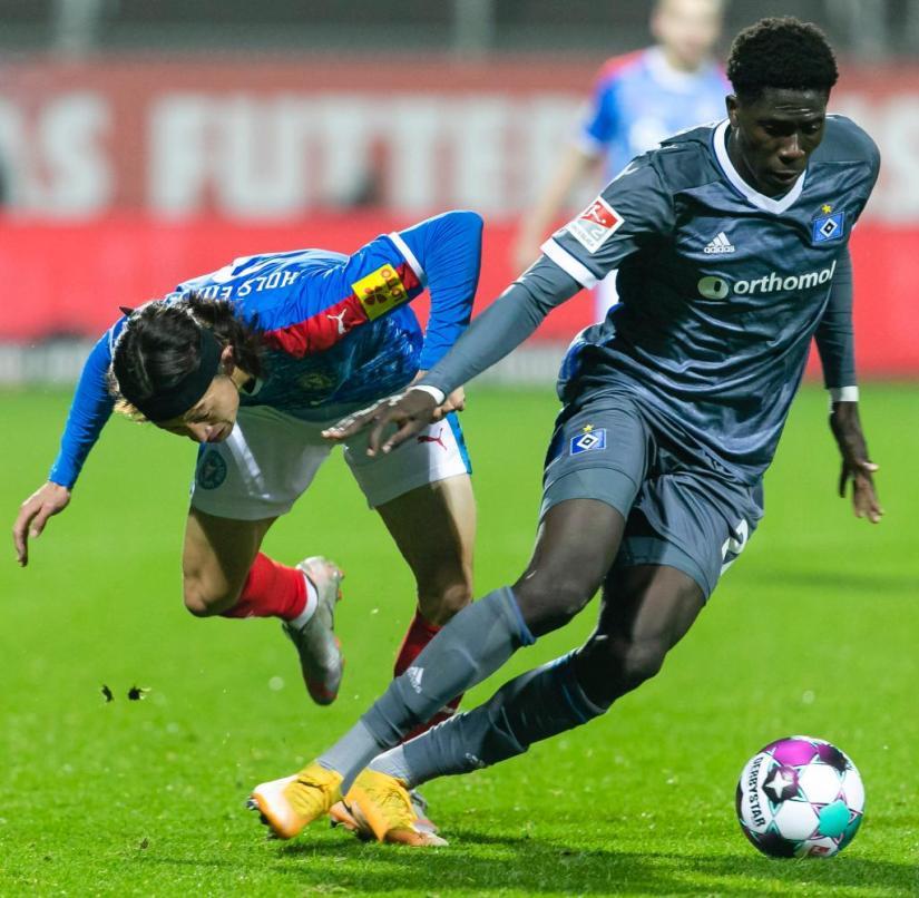 Hamburg's Amadou Onana (r.) Shields the ball against Jaeseong Lee from Kiel