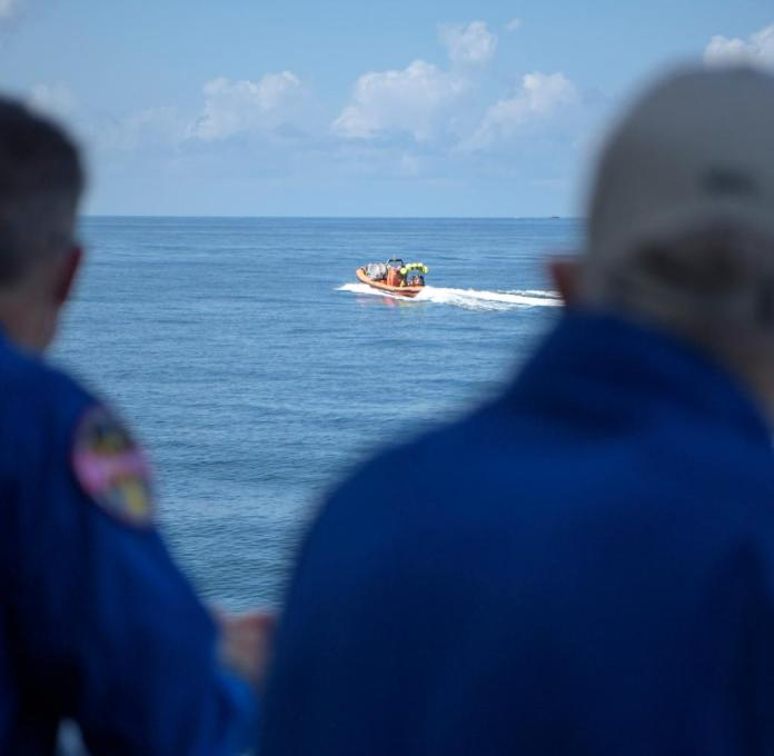 Speedboats position themselves in advance to await the arrival of the capsule