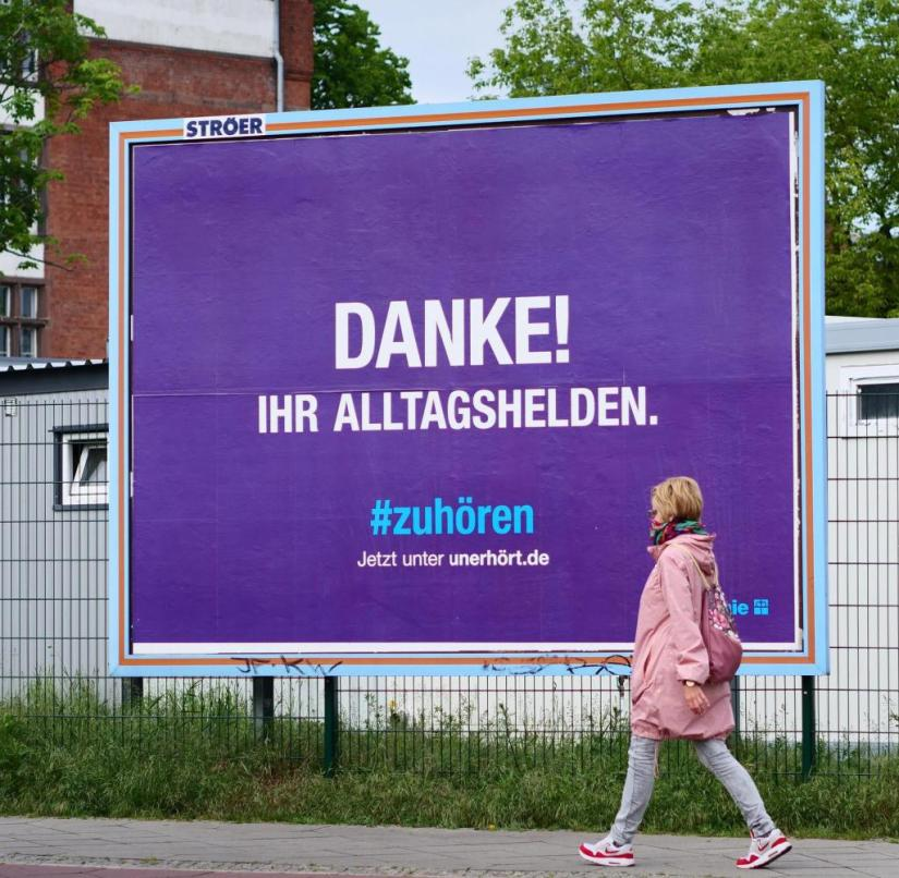 """May 24th, 2020, Berlin.  A woman wears a cloth over her mouth to protect against the novel coronavirus, while she is in front of a Diakonie poster with the inscription """"Thank you!  Your everyday hero.  #to listen.  Now at unerhoert.de"""" passes by.  Acceptance speeches, expressions of thanks and applause for people in systemically important professions in the corona crisis are controversial.  Many of those affected would prefer a wage increase rather than cheap gestures.  ATTENTION: Use only in full format.  Photo: Wolfram Steinberg / dpa    Usage worldwide"""