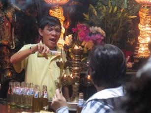 In den Flaschen gespendetes Öl wird unter lautem Sprechen von Gebeten vergossen