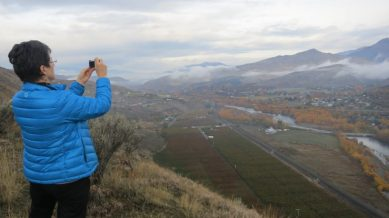 Barbee snaps a photo as Kelsay Stanton pointed out the flat terraces (often orchards) on either side of the current Wenatchee River floodplain, evidence of past river deposits.
