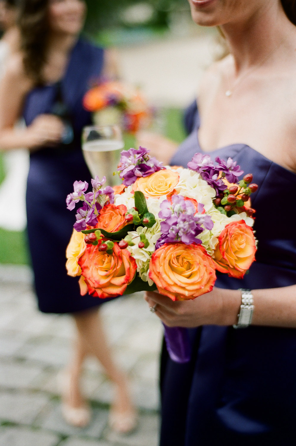 bridesmaids bouquet of orange and purple flowers by wendy g photography