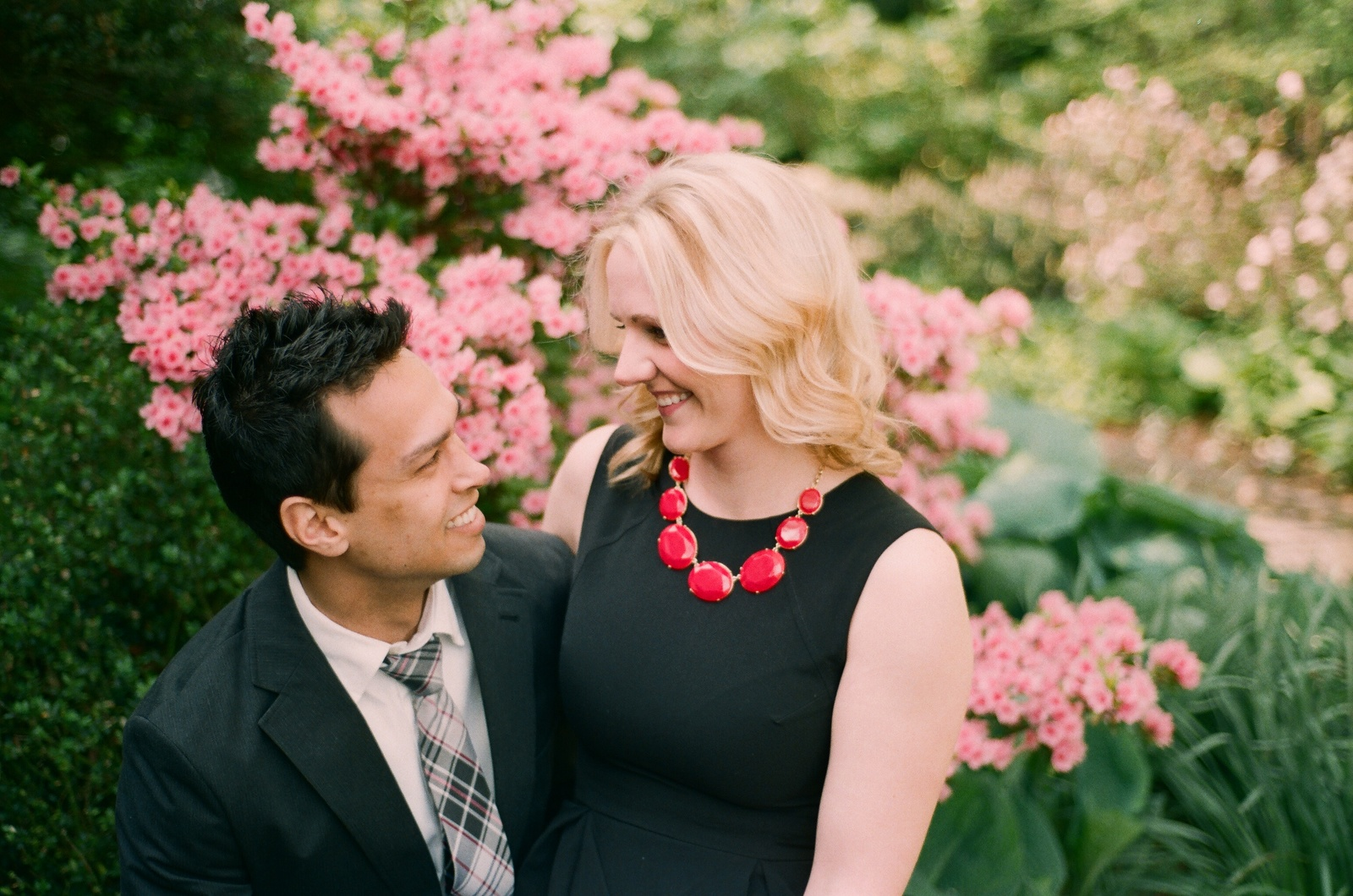 engaged couple laughing with flowers in background