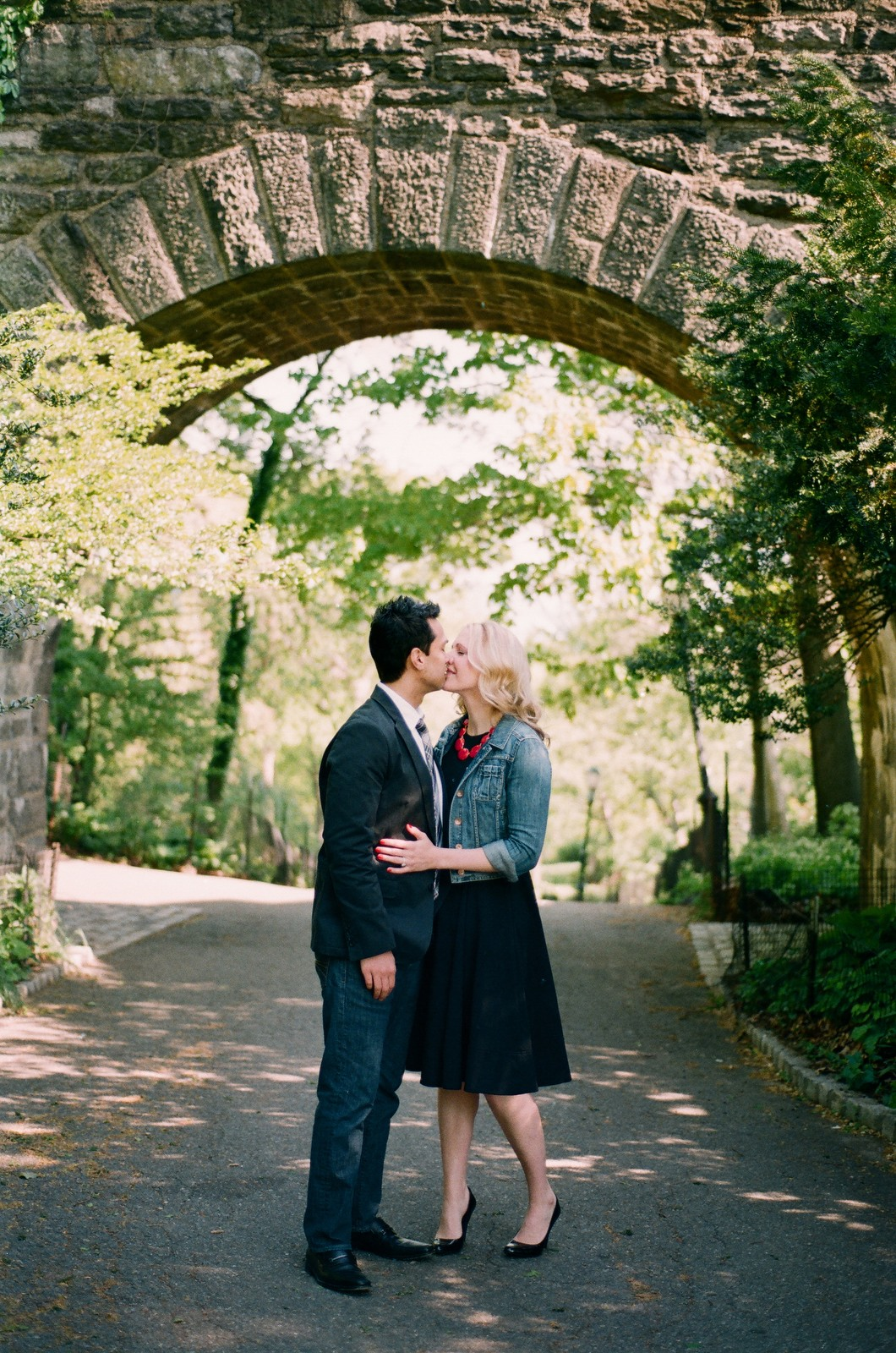 fort tryon park archway overhead of engaged couple kissing