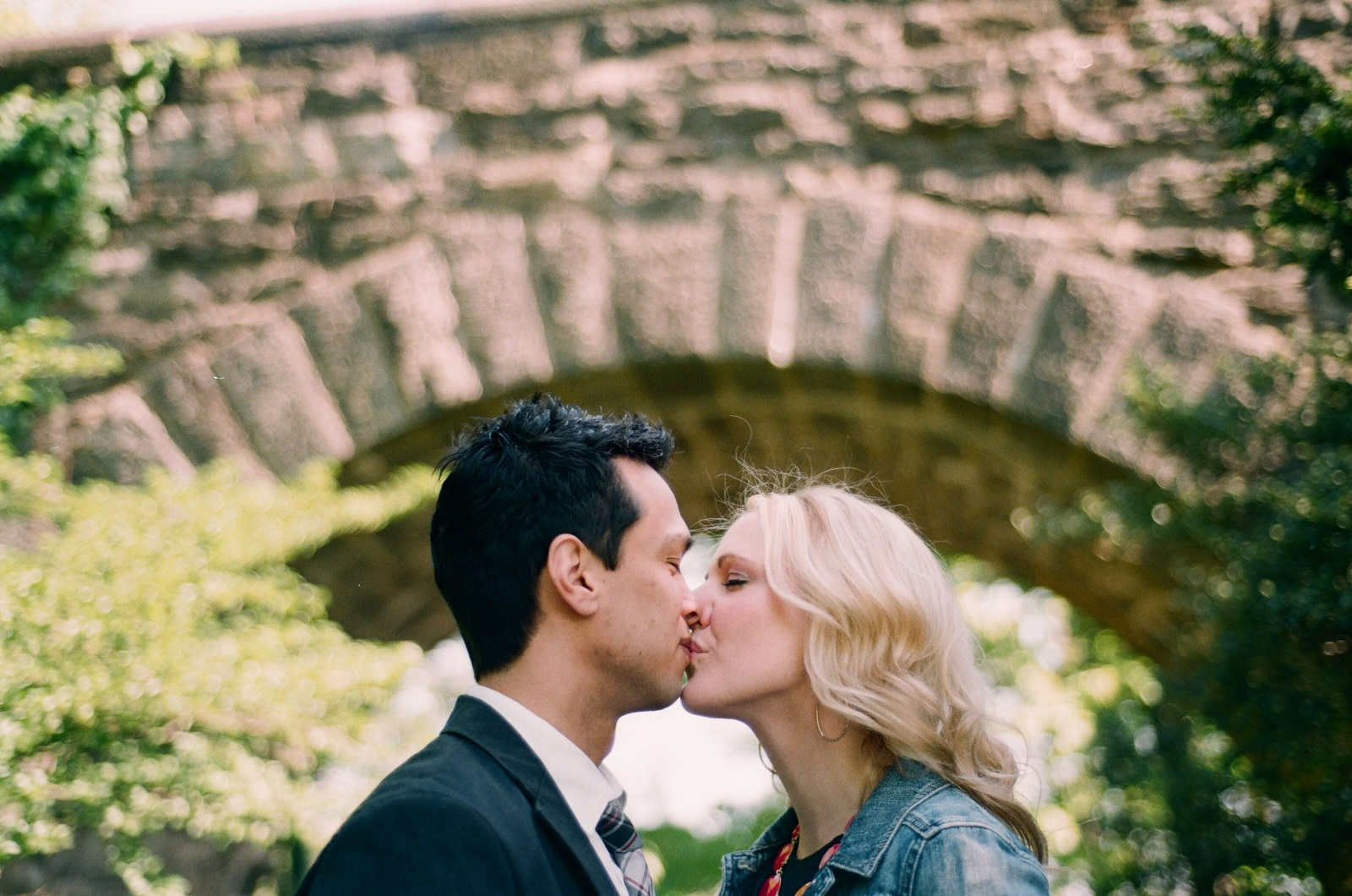 engaged couple kissing under arch fort tryon park by wendy g