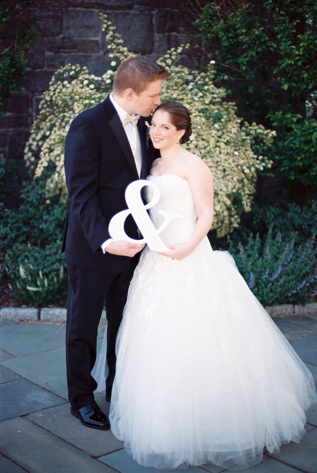 wedding couple holding ampersand sign kissing by wendy g photography