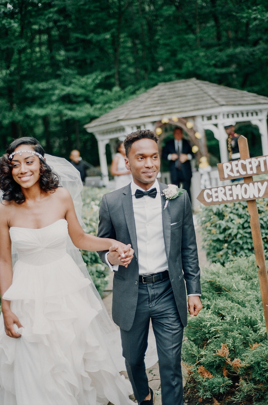 black couple holding hands coming down aisle of outdoor wedding
