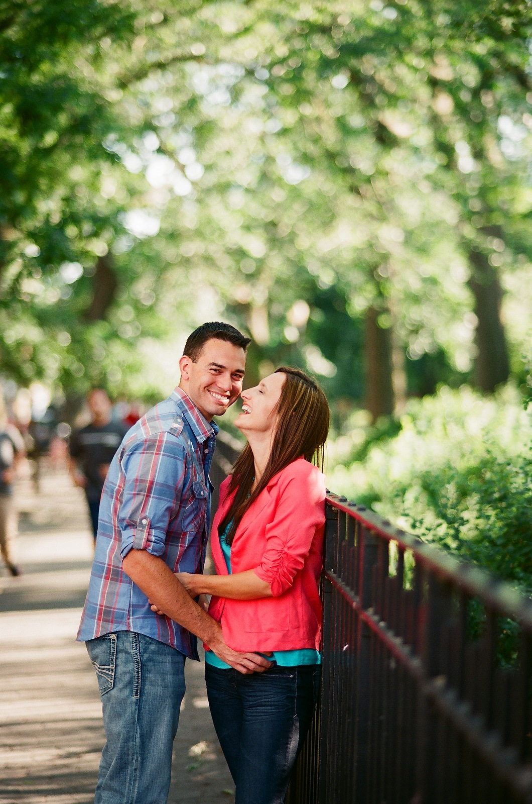 engaged couple laughing together near gate at park