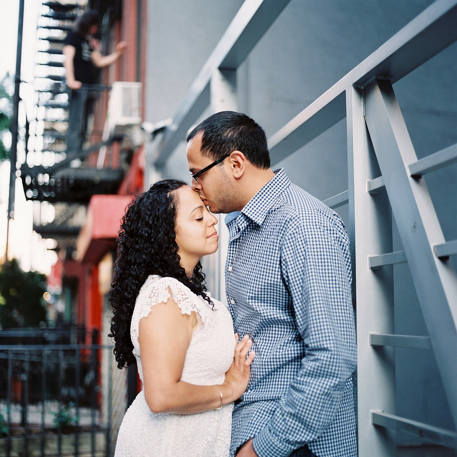 engaged couple with groom kissing bride's forehead
