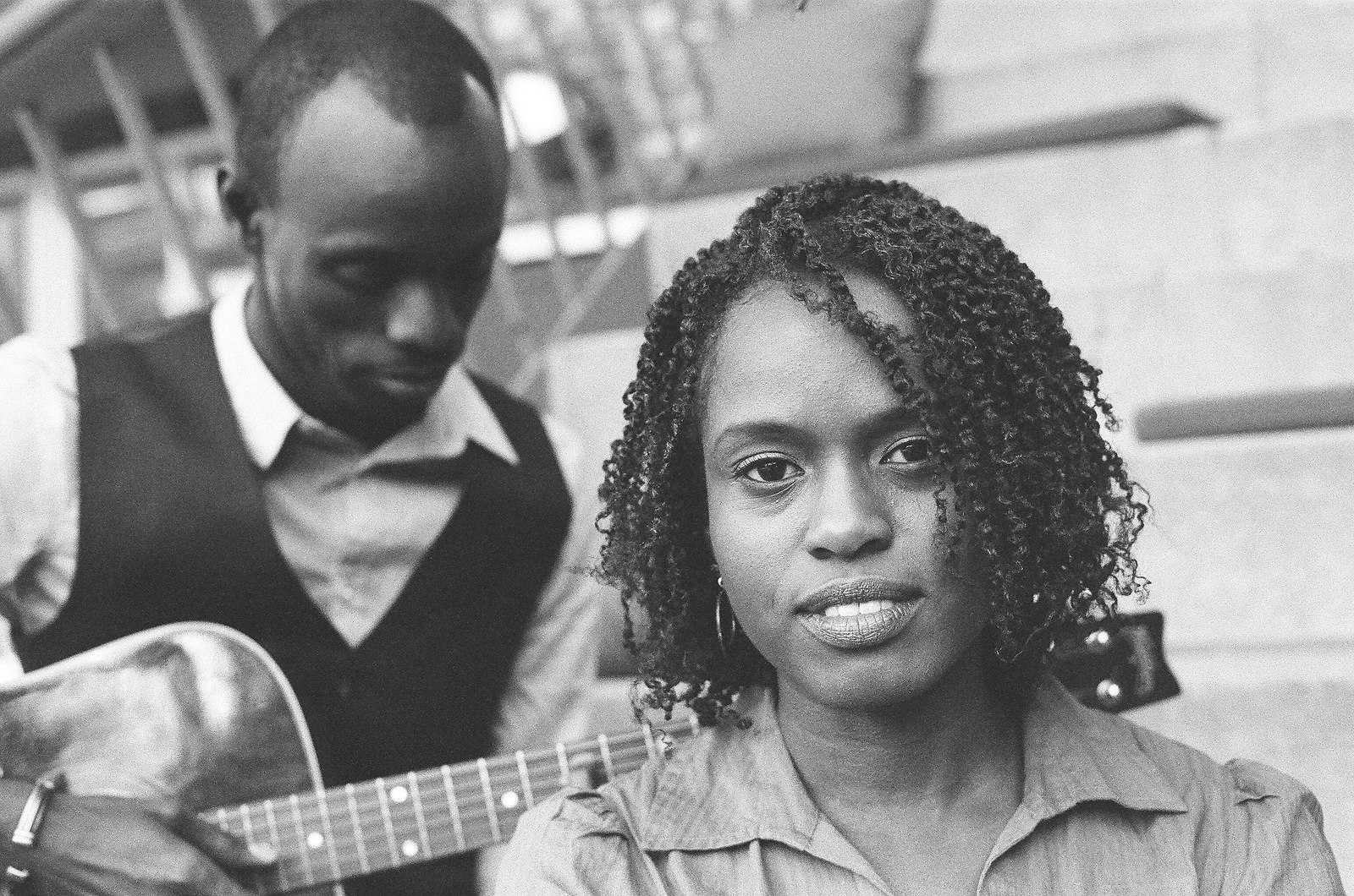 black and white photo of bride with groom holding guitar in background