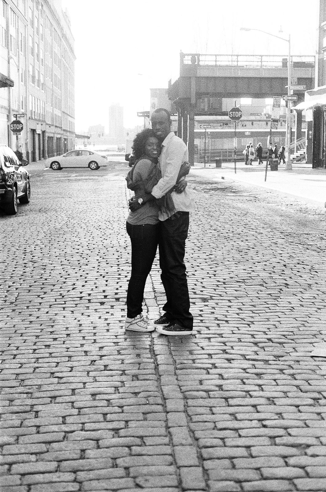 black and white photo of couple embracing on cobblestone street