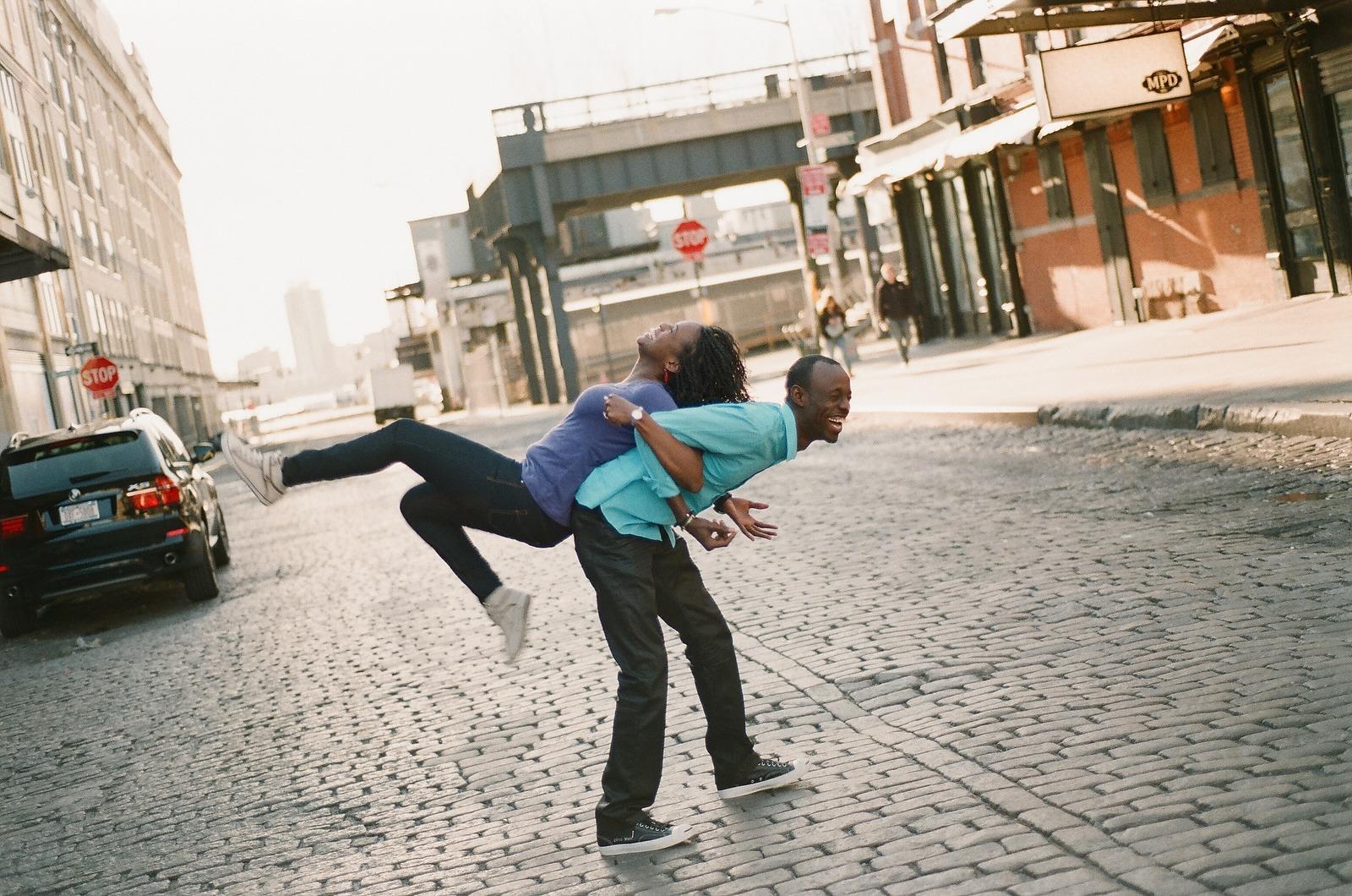 groom holding bride on his back cobblestone street